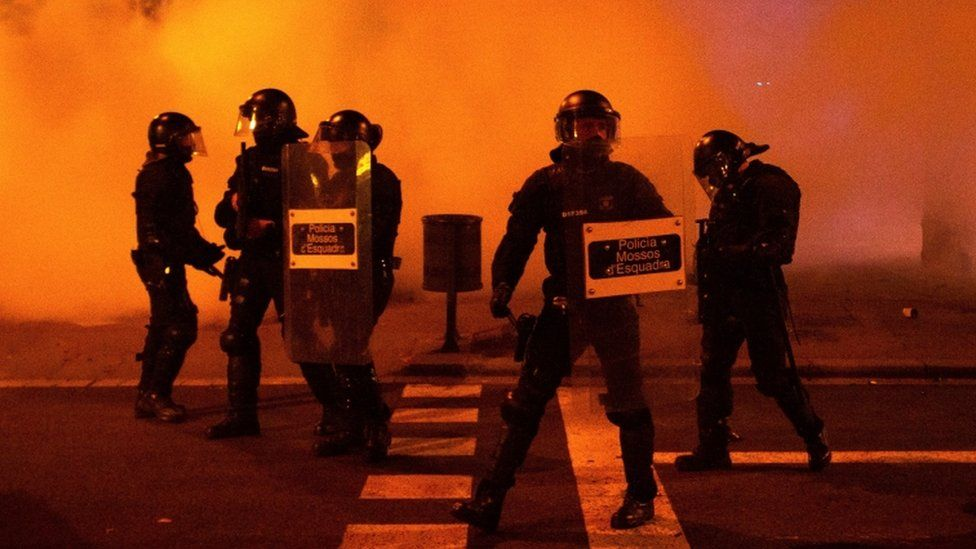 Riot police officers stand guard during a march to condemn the imprisonment of Spanish rapper