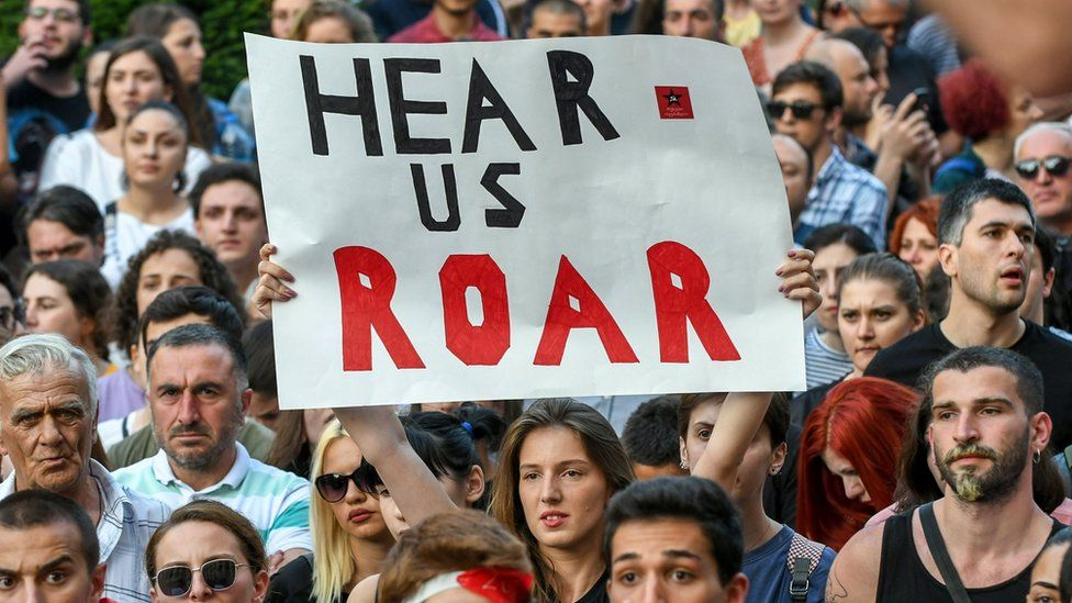 A participant holds a sign during a rally in front of the parliament building in Tbilisi on June 21, 2019