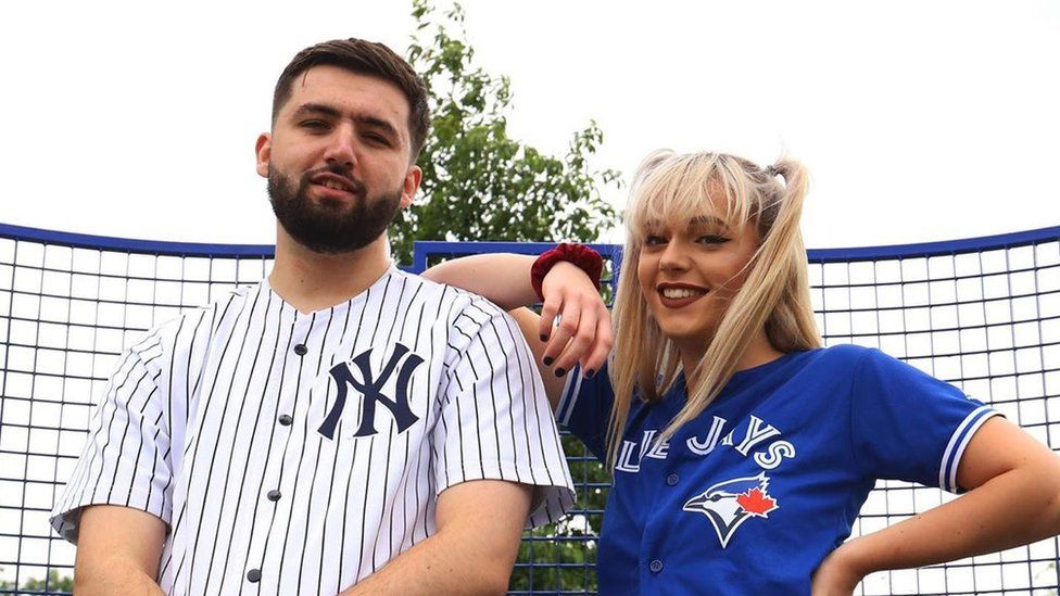 Keiran and his friend model his vintage sportswear in American baseball jerseys on a tennis court