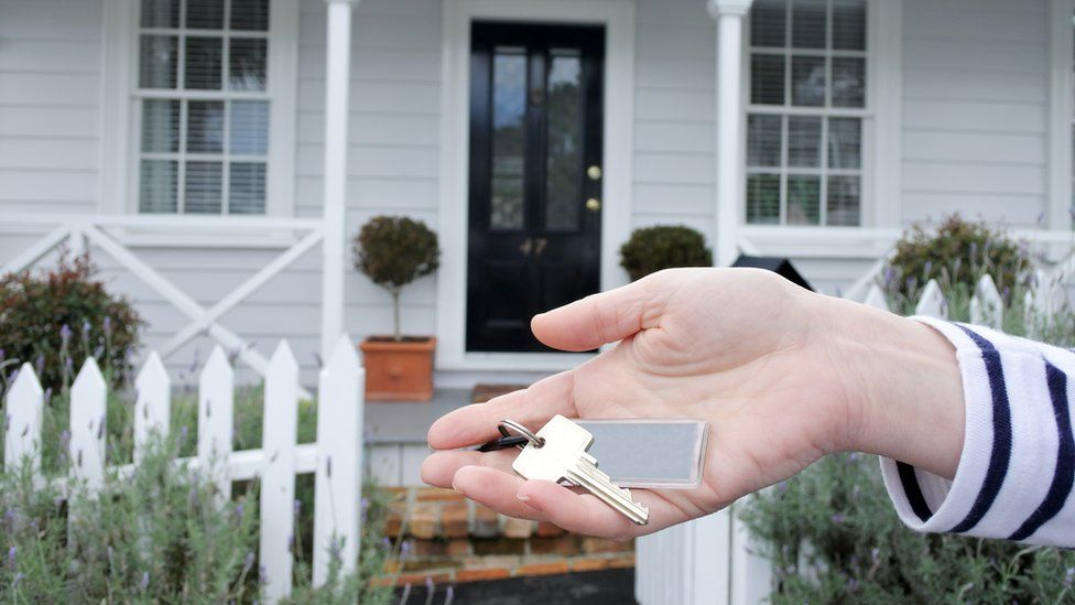 A woman holds a key outside a traditional villa house in Auckland, New Zealand. File photo