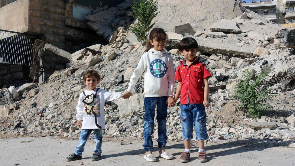 Bana posing for a picture with her brothers amid the rubble of a destroyed building