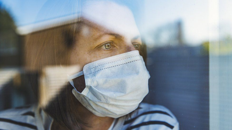 woman looking out of window wearing mask