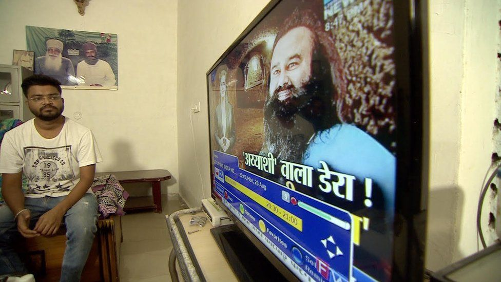 A man watches Singh on his television screen