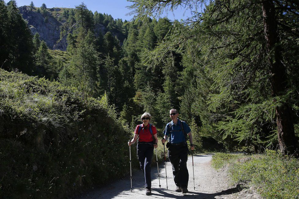 UK Prime Minister Theresa May walks with her husband Philip in Swiss Alps, 12 Aug 16