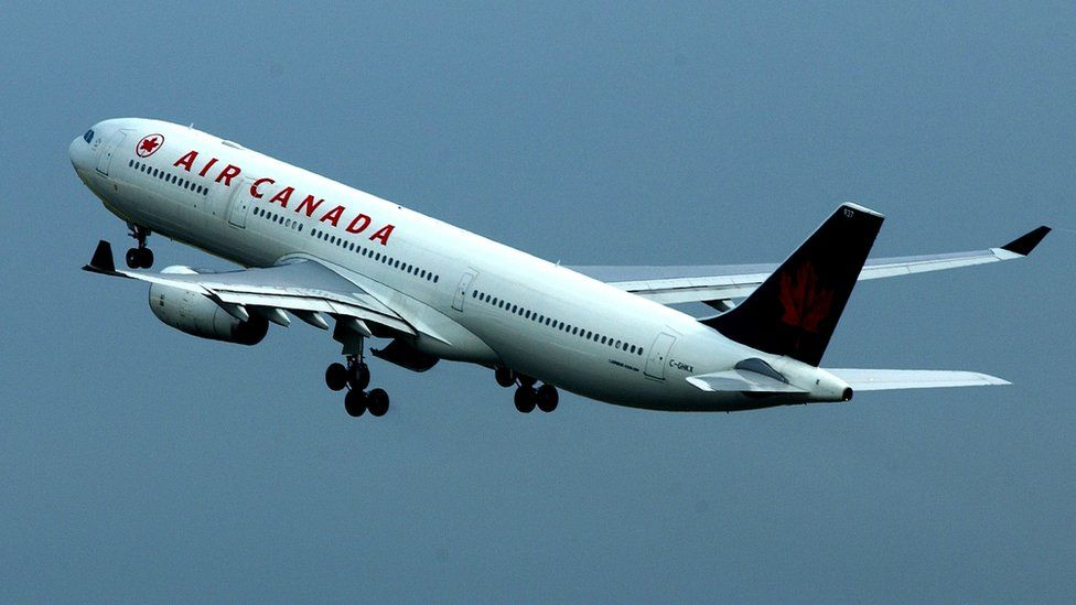 An Air Canada passenger plane is shown in flight at Heathrow Airport July 31, 2002 in London, England.