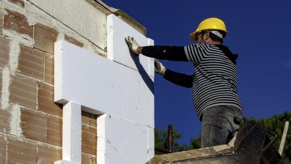 A man adding external wall insulation to a house