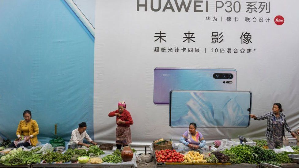 Women sell vegetables in front of a billboard advertising smartphones for China's Huawei Technologies Co., on June 1, 2019 in Mangshi, Yunnan Province, southwestern China