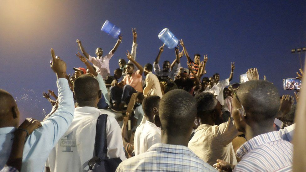 People holding large plastic water containers cheering at a sit-in at the military HQ in Khartoum, Sudan - Sunday 7 April 2019