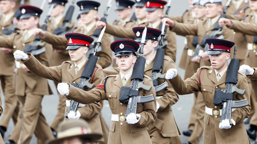 Junior soldiers in a row performing in a parade while carrying rifles