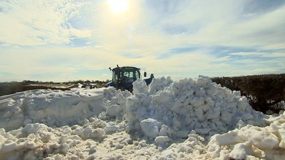 A tractor helps clear deep snow from a road in Vale of Glamorgan