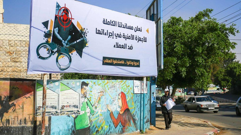 """A man walks past a banner in Gaza City that says: """"We declare our full support for the security authorities in their measures against collaborators"""" and """"They betrayed, and backstabbed, and deserved the punishment"""" (5 April 2017)"""