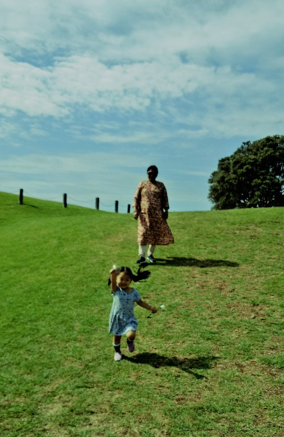 A young girl runs in front of her grandmother in a field
