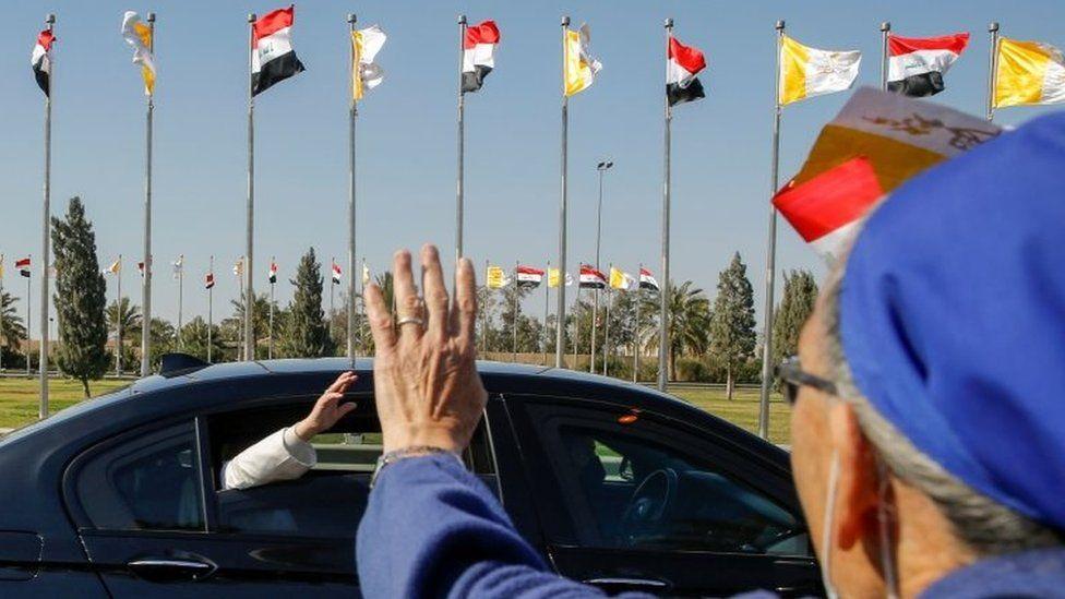 El Papa Francisco saluda mientras su convoy se dirige a Bagdad desde el aeropuerto