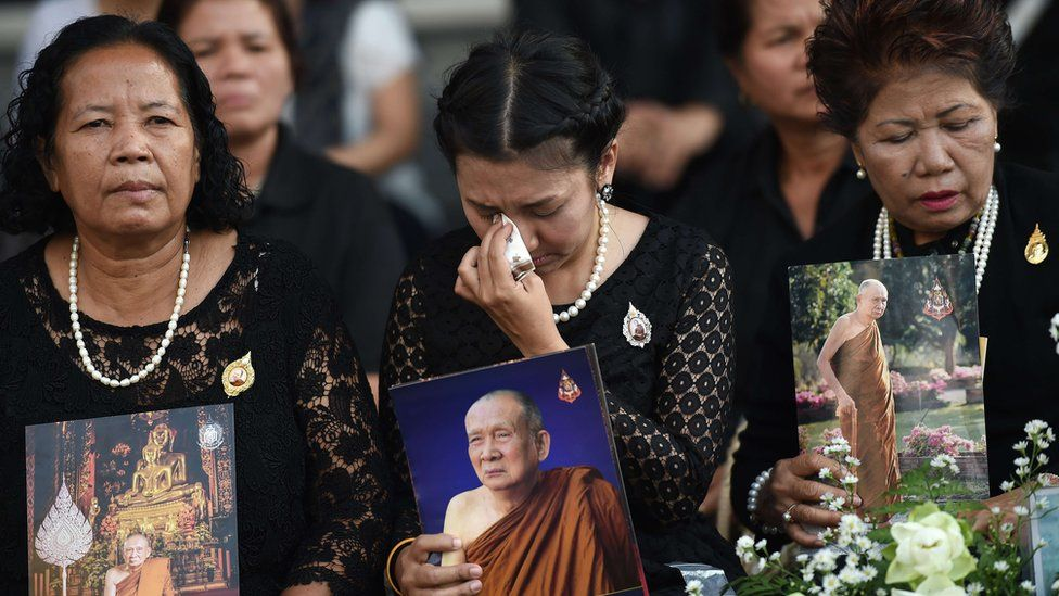 """Women hold pictures of Thailand""""s most senior Buddhist monk, the late Supreme Patriarch Somdet Phra Nyanasamvara"""