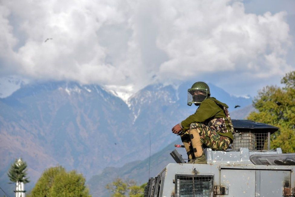 An Indian paramilitary trooper sits on the roof of the police vehicle during clashes in Srinagar in 2018.