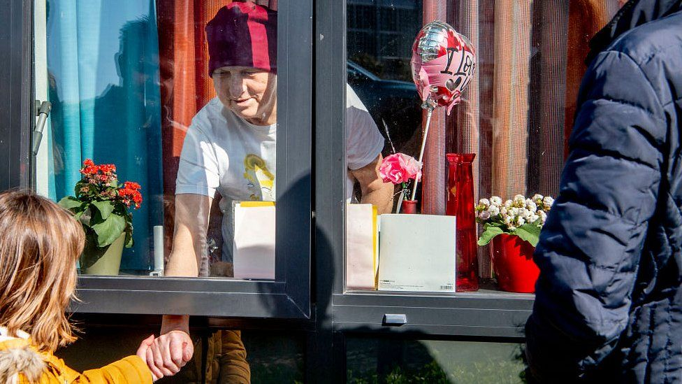 Reijnen family in Tilburg, Netherlands, saying goodbye to grandmother Van Baast behind a window of a care home as the only protective measure against the spread of coronavirus. 28 March 2020
