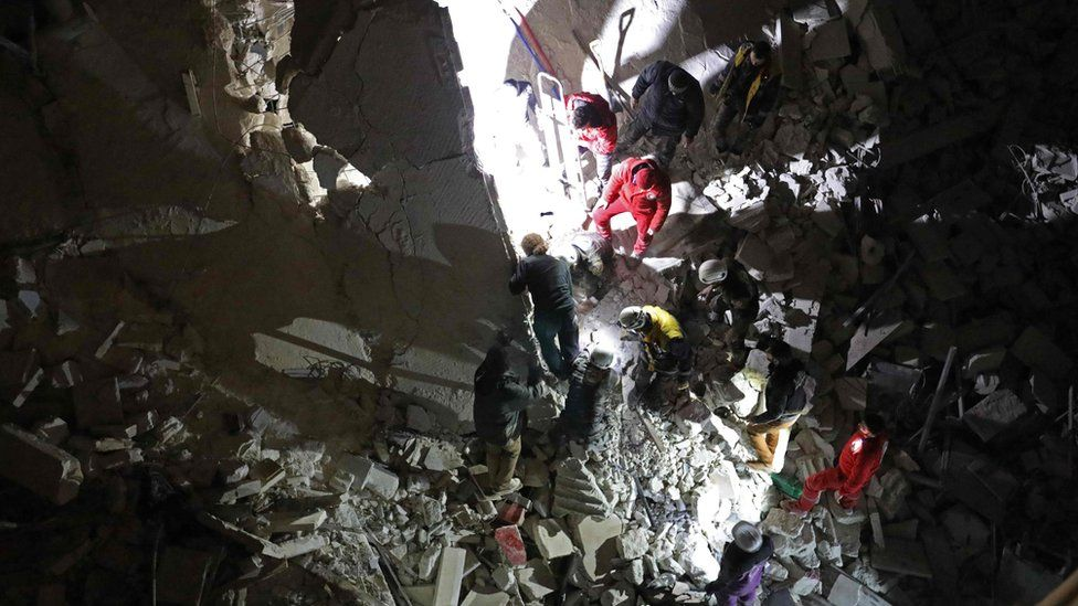 Rescue workers search for survivors in the remains of a block of flats destroyed in a reported air strike in Idlib city (4 February 2018)
