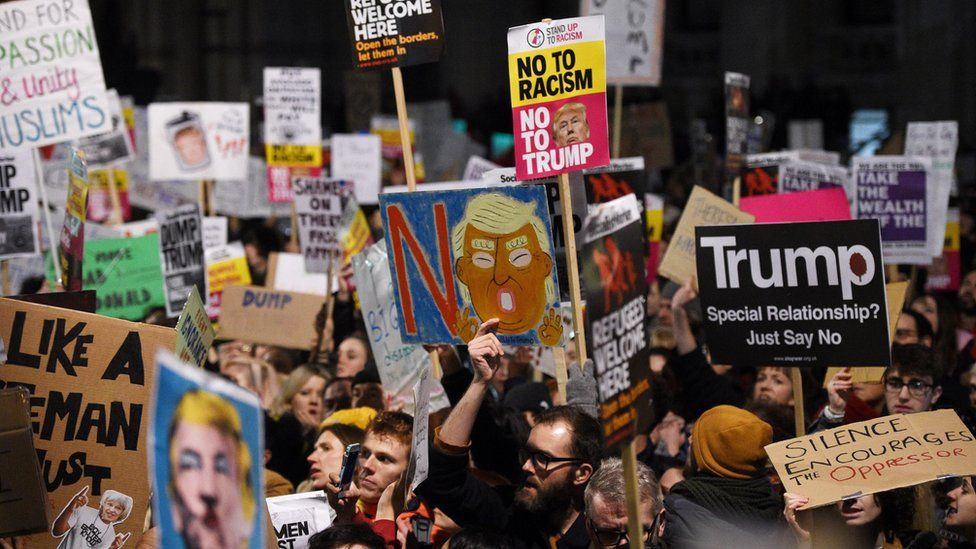Protesters hold banners during a demonstration outside 10 Downing Street in London (30 January 2017)