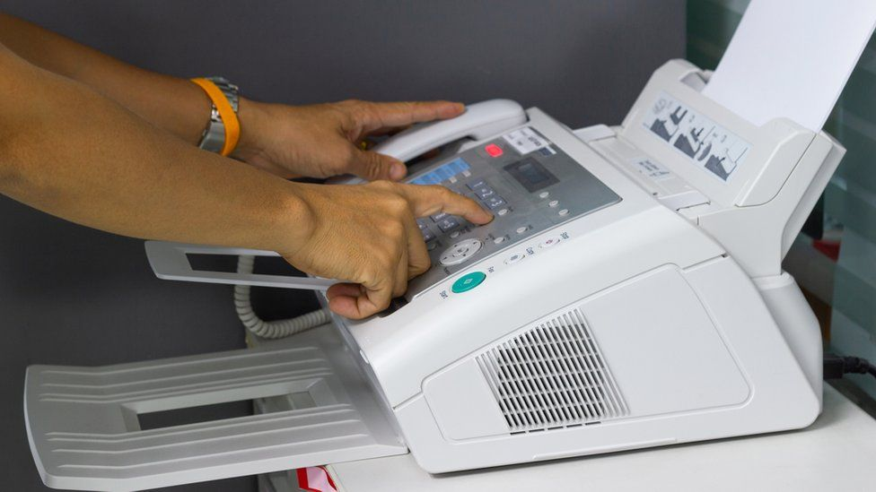 Someone using a fax machine