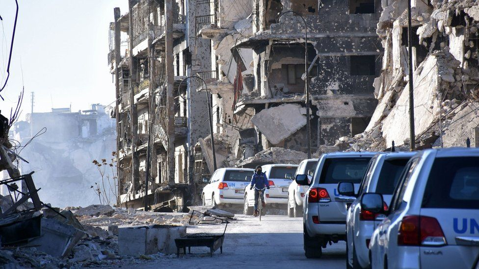 A UN convoy drives past damaged buildings in the eastern neighbourhoods of Syria's second city of Aleppo, on February 1, 2017