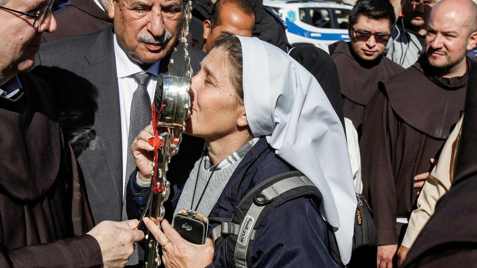 A nun kisses the relic during a procession in Bethlehem, 30 November 2019
