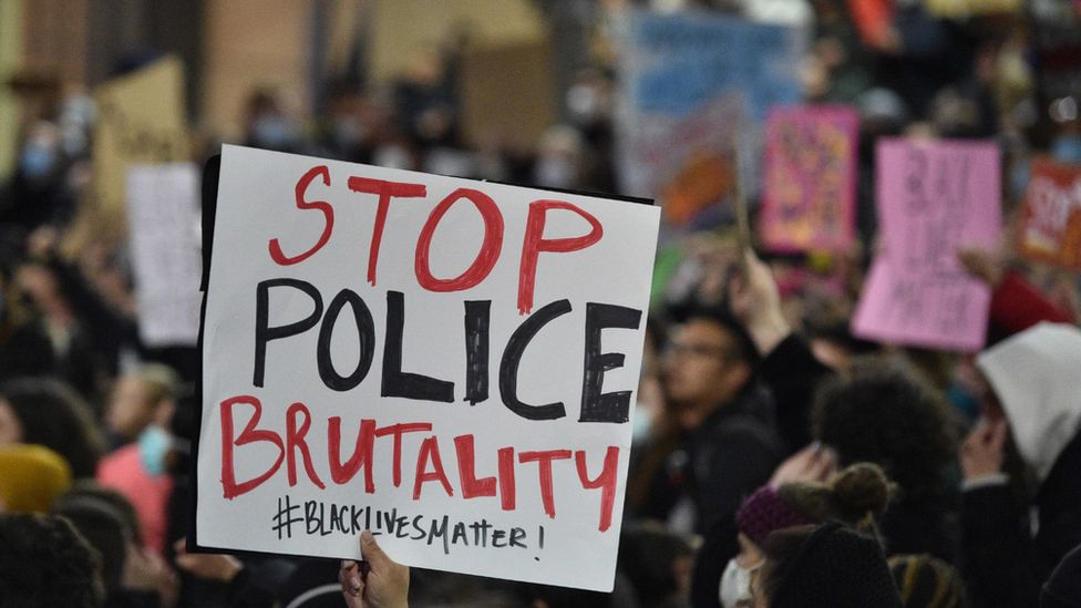 A protester at Sydney's Black Lives Matter rally holds up a 'Stop Police Brutality' sign