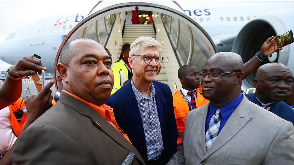 Former soccer coach Arsene Wenger (C) is greeted by Zoegar Wilson (R), Liberia's minister of Youth and Sports, as he arrives at the Roberts International Airport in Harbel, Liberia, 22 August 2018.