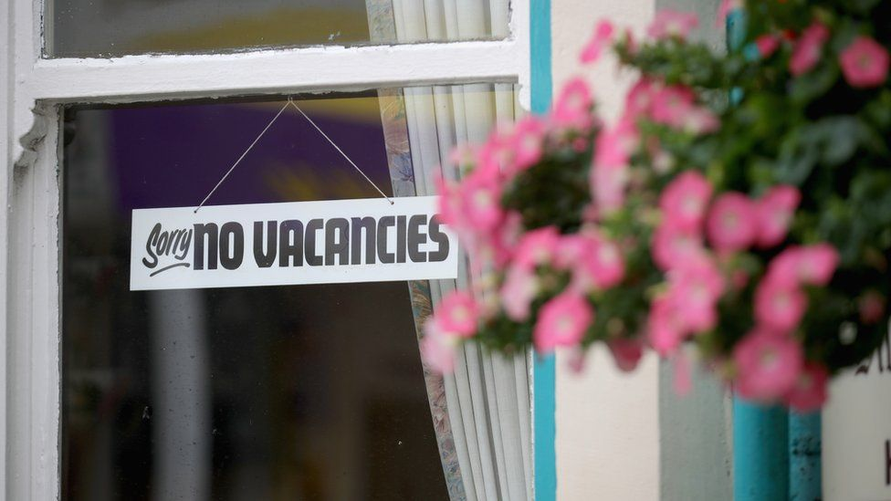 """A """"No Vacancies"""" sign hangs in the window of a Bed and Breakfast guest house"""