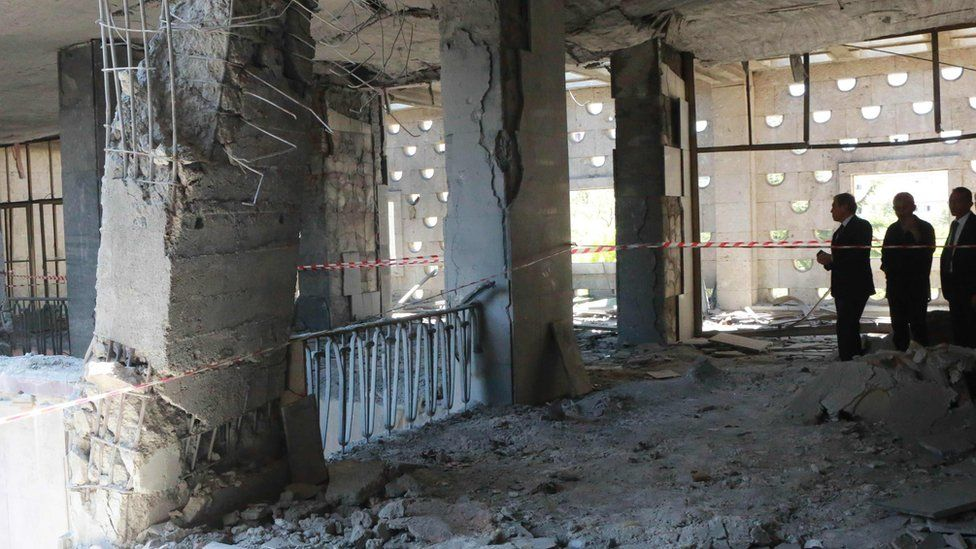 Men inspect damage after Turkey's parliament was bombed by rebel jets (16/07/2016)