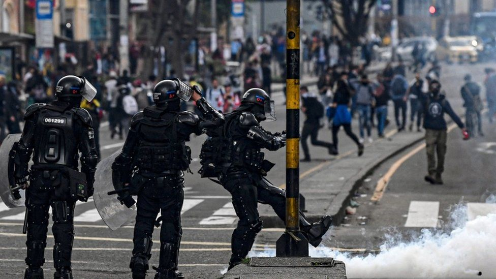 A riot policeman kicks a tear gas canister during a protest in Bogota