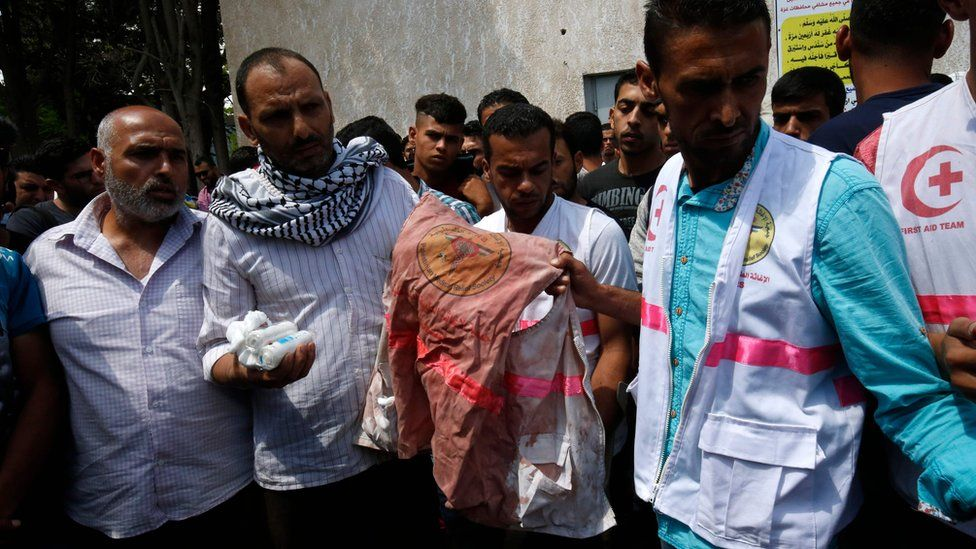 Father (second left) of Razan al-Najar holds her jacket covered with blood during her funeral in Khan Younis on June 2, 2018
