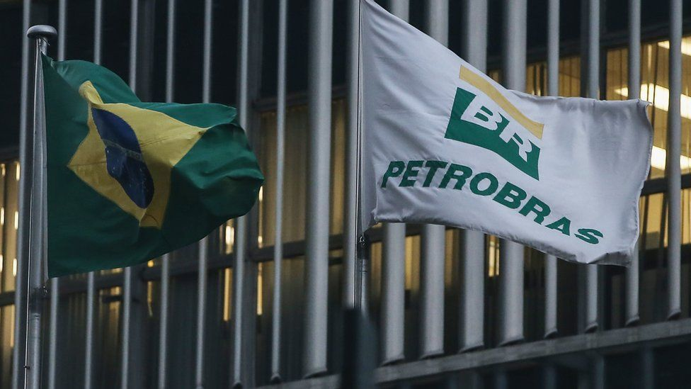 A Brazilian flag and a Petrobras flag fly in front of Petrobras headquarters in Rio de Janeiro on 13 April, 2016