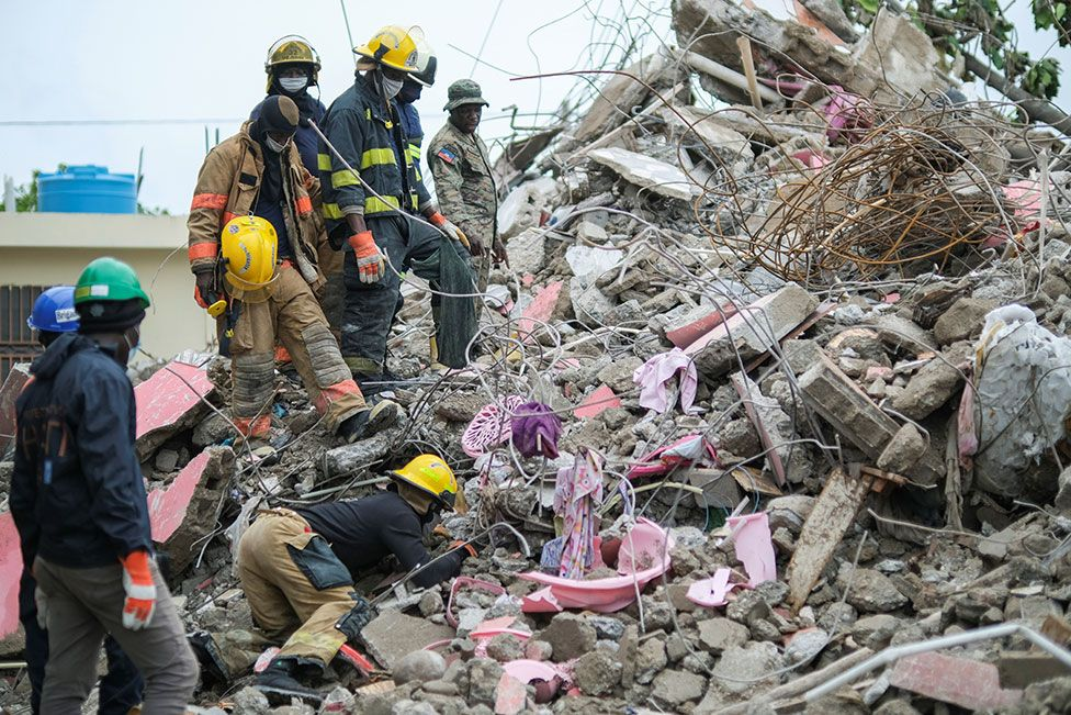 Haitian firefighters search for survivors under the rubble of a destroyed building in Les Cayes, Haiti, on 17 August 2021