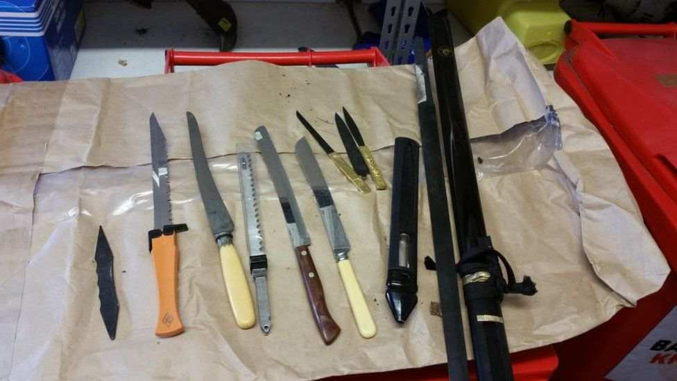 Several knives and weapons laid out on a table