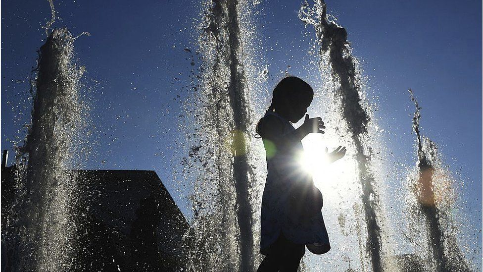 Child in fountain on warm summer's day in Moscow