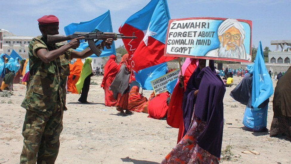 A Somali security soldier points his weapon at a poster bearing a photo of Al-Qaeda leader Ayman al-Zawahiri during an anti Al-Shabab rally in Mogadishu on February 23, 2014