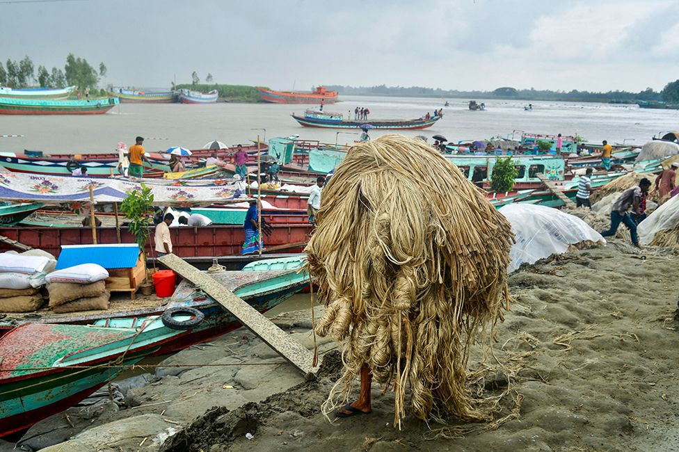 A worker carries jute to a boat at a rural market in Munshigonj, Bangladesh, on 17 September 2021