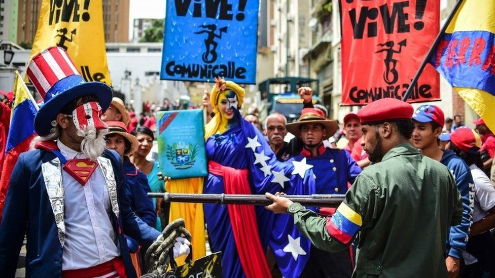 Pro-government activists representing a Venezuelan Bolivarian revolutionary (R) and Uncle Sam (L) perform during a demonstration to support President Nicolas Maduro, in Caracas, on August 14, 2017.