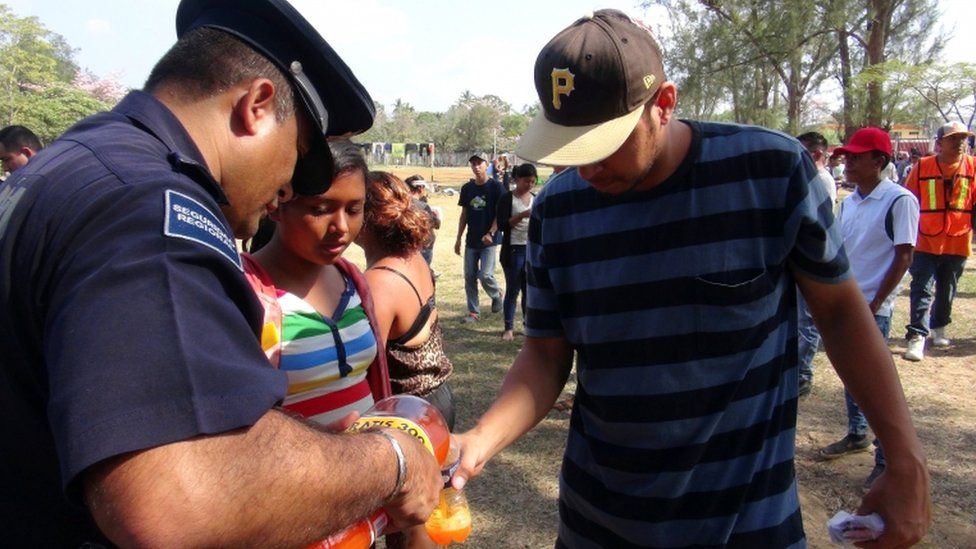 A Mexican police officer pours a soft drink for a migrant