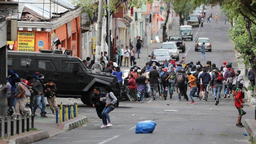 Demonstrators run away from an armoured vehicle during protests against fuel subsidy cuts
