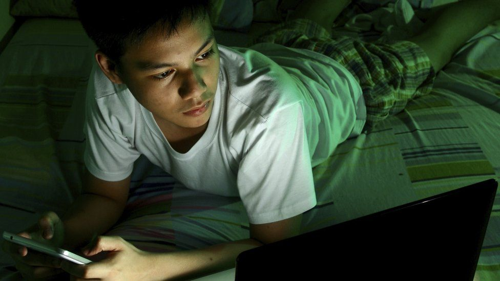Child on phone in bed at night