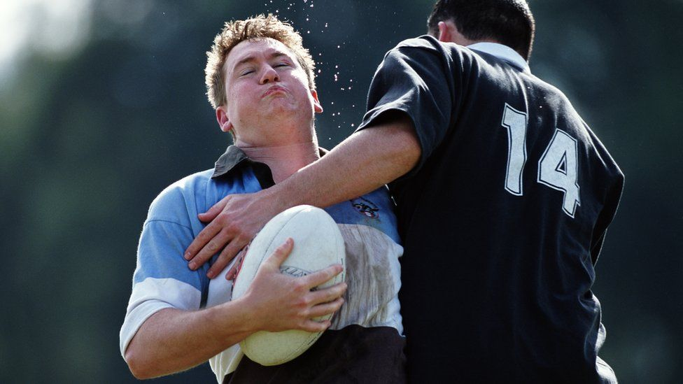 Male rugby player being caught in a tackle