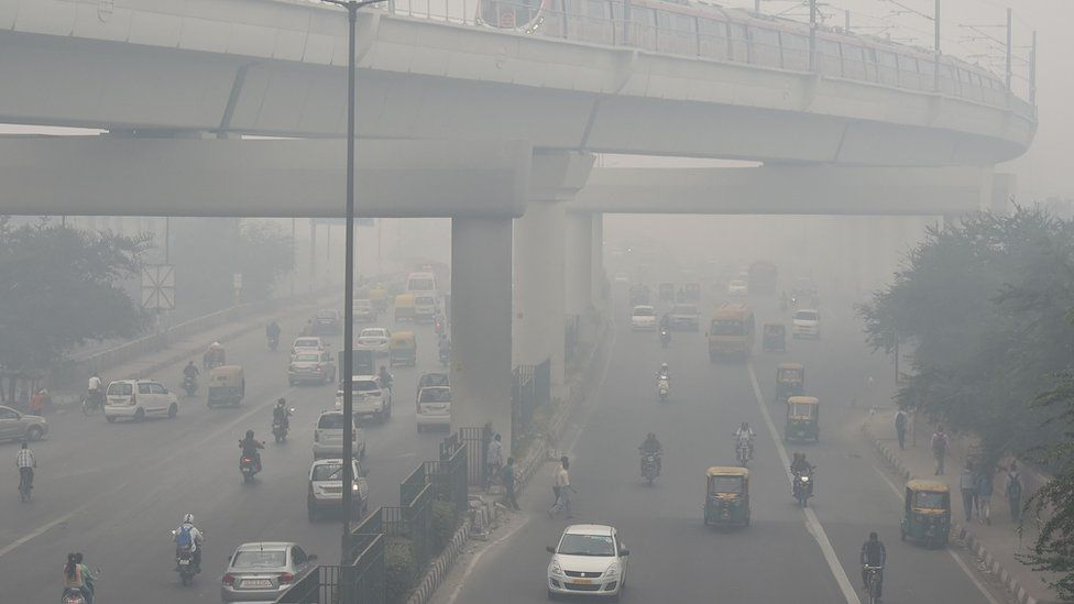 A Delhi Metro train (top) and vehicles drive past amid heavy smog in New Delhi on November 5, 2018