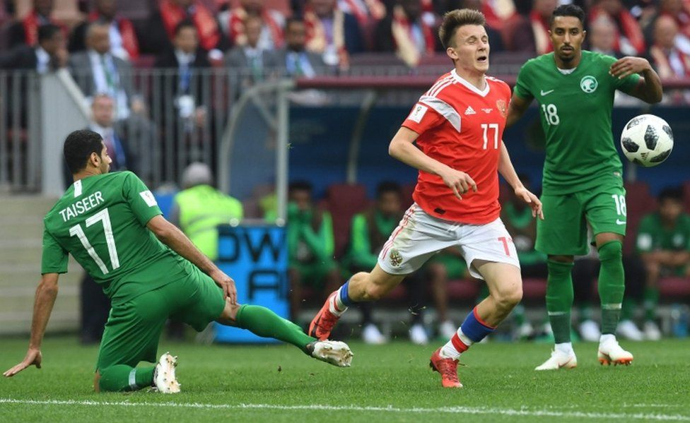 Russia's Aleksandr Golovin is tackled during the 2018 World Cup match between Russia and Saudi Arabia on 14 June, 2018