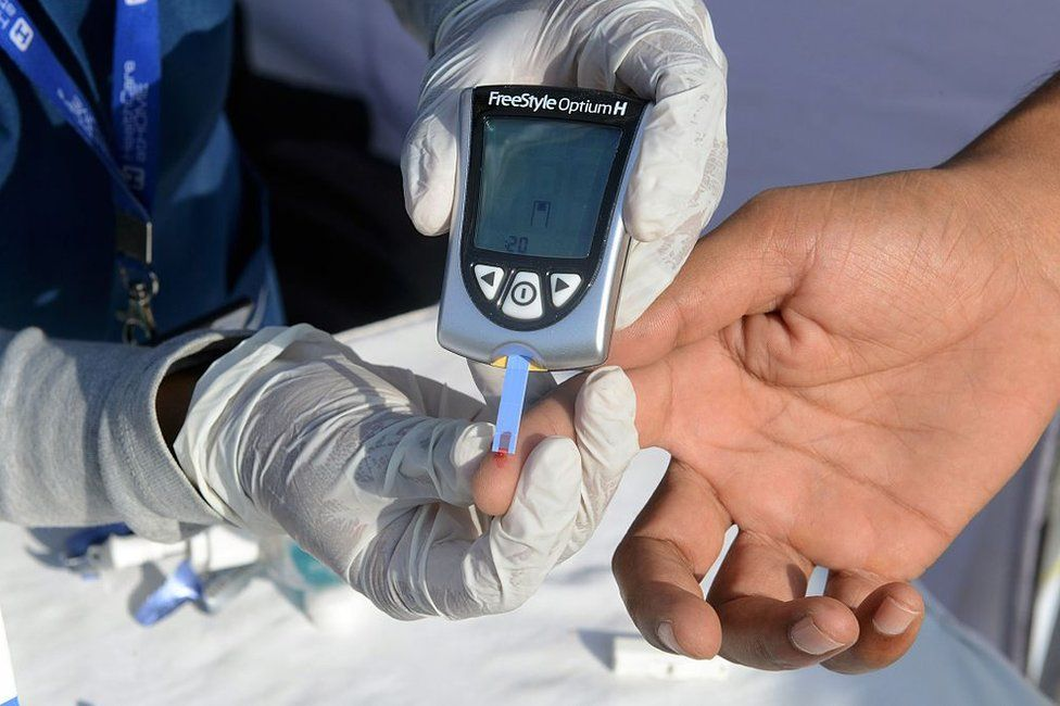 An Indian nurse (L) collects a blood sample from a policeman using a glucometer at a free diabetic health check-up camp on World Health Day in Hyderabad on April 7, 2016
