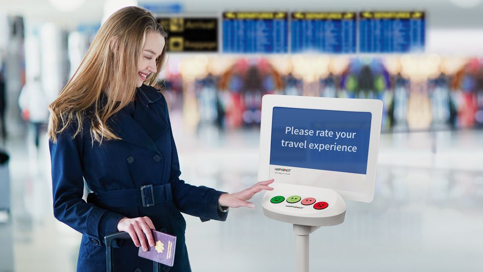 A woman using a Happy Or Not terminal at an airport
