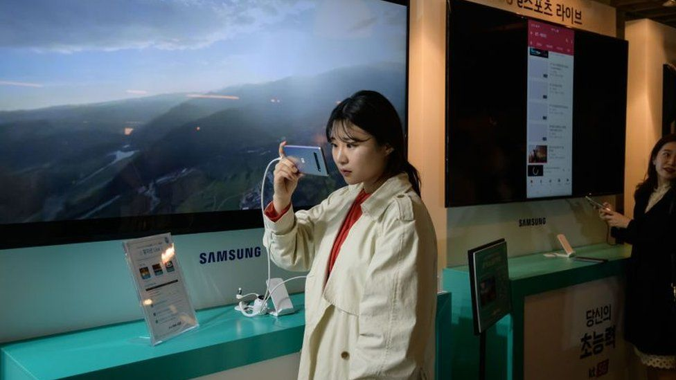 Woman looks at looks at a Samsung Galaxy S10 5G smartphone during a Korea Telecom 5G launch event in Seoul on 5 April 2019