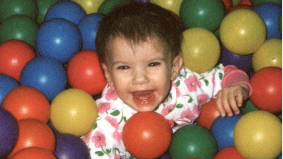 A photograph shows Baylee in a ball pool