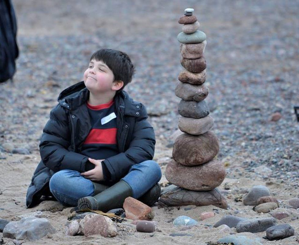 Boy with large stack of stones