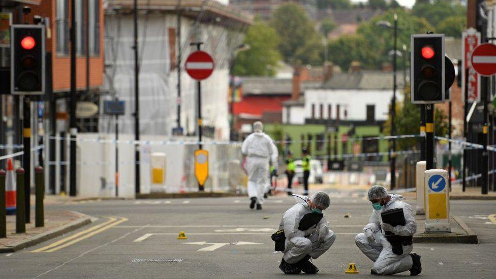 Police forensics officers gather evidence inside a cordon on Hurst Street